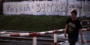 """Un hombre camina frente a un graffiti que dice """"patria o buitres"""" en Buenos Aires. Imagen de archivo, 24 agosto, 2014.  El Congreso argentino se preparaba el miércoles para convertir en ley un proyecto impulsado por el Gobierno para permitir pagar en Buenos Aires a los bonistas que se han visto impedidos de cobrar en el extranjero por una decisión judicial en Estados Unidos. REUTERS/Marcos Brindicci"""