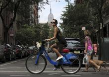 The Empire State Building is seen in the distance as a woman rides a Citibike in the Soho neighbourhood of New York July 27, 2013. REUTERS/Gary Hershorn