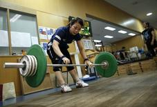 Japanese weightlifter and captain of Japan's athletes for the Asian Games Hiromi Miyake works out at the National Training Center in Tokyo September 5, 2014. REUTERS/Issei Kato