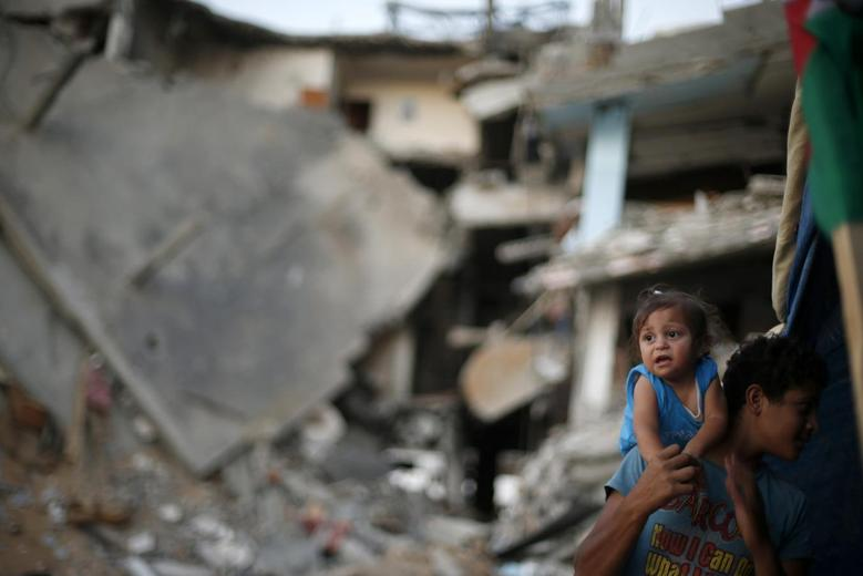 A Palestinian boy holds his sister near the ruins of their family's house, which witnesses said was destroyed during the Israeli offensive, in the east of Gaza City September 10, 2014.  REUTERS/Suhaib Salem