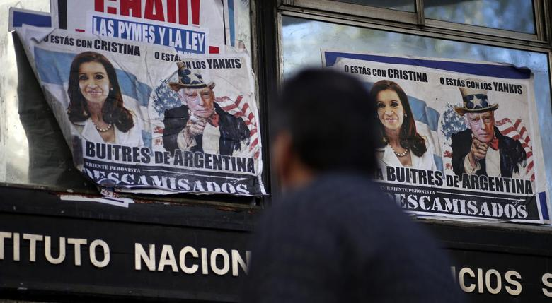 A man walks past posters with pictures of Argentina's President Cristina Fernandez de Kirchner and U.S. District Court for the Southern District of New York Judge Thomas Griesa, depicted as Uncle Sam, near the Argentine Congress in Buenos Aires, September 10, 2014.   REUTERS/Marcos Brindicci
