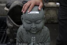 An Jianxing, a 50 year old gravestone business owner and designer, touches a head of his designed little Buddha statue, which has a price label on for closing sale, at his company showroom in Ibaraki prefecture, north of Tokyo September 10, 2014. REUTERS/Yuya Shino
