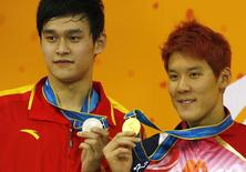 Gold medal winner Park Tae-hwan (R) of South Korea stands with silver medal winner Sun Yang of China during the medal ceremony for the men's 200m freestyle swimming event at the 16th Asian Games in Guangzhou, Guangdong province, November 14, 2010.   REUTERS/David Gray
