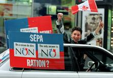 "A ""NO"" supporter reacting from a moving car while taking his message through the streets of down town Montreal, Quebec, in this October 30, 1995 file photo.  REUTERS/Mike Blake/Files"