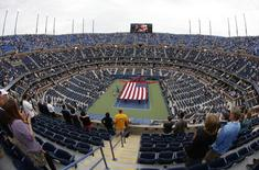 Tennis fans watch amid empty seats as U.S. Marines unfurl a large U.S. flag during ceremonies ahead of the men's singles final match between Kei Nishikori of Japan and Marin Cilic of Croatia at the 2014 U.S. Open tennis tournament in New York, September 8, 2014.  REUTERS/Shannon Stapleton