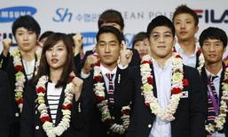 South Korea's Kim Hyeon-woo (front R), gold medalist of the Men's 66Kg Greco-Roman wrestling at the London 2012 Olympic Games, poses with other athletes upon South Korean national team's arrival from London, at Incheon international airport in Incheon, west of Seoul August 14, 2012.   REUTERS/Kim Hong-Ji