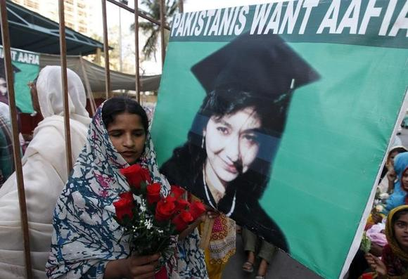 An Aafia Siddiqui supporter carries silk roses next to a poster during a celebration to mark Siddiqui's 41st birthday in Karachi March 2, 2014. REUTERS/Akhtar Soomro/Files