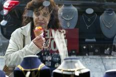 Женщина изучает витрину ювелирного магазина Gold Standard в Нью-Йорке 15 апреля 2013 года. Цены на серебро упали до четырехлетнего минимума на фоне укрепления доллара. REUTERS/Lucas Jackson