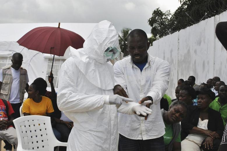 A volunteer health worker practises using a personal protective equipment (PPE) suit at a newly-constructed Ebola virus treatment centre in Monrovia, Liberia, September 21, 2014. REUTERS/James Giahyue