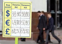 Люди идут по улице мимо пункта обмена валюты в Москве 16 сентября 2014 года. Рубль торгуется в минусе на биржевой сессии понедельника из-за локального спроса на валюту, вкупе с негативными тенденциями мировых рынков, перебивающими положительный эффект экспортных продаж в пик налогового периода. REUTERS/Sergei Karpukhin