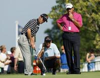 Mike Weir (L) of Canada putts on the practice green as his caddie Brennan Little (C) and sports psychologist Bob Rotella look on during a practice day for the 2009 PGA Championship golf tournament at Hazeltine National Golf Club in Chaska, Minnesota, August 12, 2009. REUTERS/Eric Miller