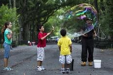 Children watch as artist Manny Ford performs with soap bubbles in New York City's Central Park, August 23, 2013. REUTERS/Lucas Jackson