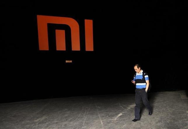 9月24日、台湾は中国スマホメーカー、小米科技を調査していると発表した。写真は同社のロゴマークと携帯電話を確認する人。北京で2012年8月撮影(2014年 ロイター/Jason Lee)