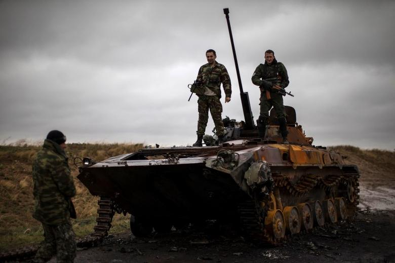 Pro-Russian rebels stand on top of a burnt-out Ukrainian armoured personnel carrier near the village of Novokaterinovka, eastern Ukraine, September 24, 2014.  REUTERS/Marko Djurica