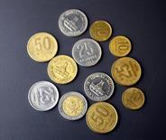 """Monedas argentinas son mostradas en Buenos Aires. Imagen de archivo, 06 noviembre, 2007. El Gobierno argentino dijo el jueves que el valor del peso en el mercado cambiario oficial está en """"convergencia"""" con la cotización de otras divisas internacionales, en un intento por defender a la moneda luego de que su valor en el mercado negro se desplomara por temor a una devaluación. REUTERS/Enrique Marcarian"""