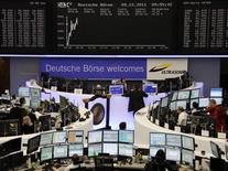 "Traders work at their desks in front of the German share price index DAX board and a banner reading ""Deutsche Boerse Welcomes Ultrasonic"" at the Frankfurt stock exchange December 9, 2011.    REUTERS/Remote/Kirill Iordansky"