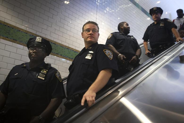 Policemen ride down an escalator as they can patrol the Times Square subway station in the Manhattan borough of New York September 25, 2014. REUTERS/Carlo Allegri