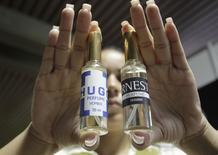 "A worker at LABIOFAM, the Cuban state manufacturer of medicinal and personal hygienic products, holds up bottles of Hugo and Ernesto perfume named after socialist icons Hugo Chavez and Ernesto ""Che"" Guevara, in Havana September 25, 2014. REUTERS/stringer"