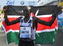 Dennis Kimetto of Kenya holds up his national flag as he celebrates winning the 41st Berlin marathon, September 28, 2014. REUTERS/Hannibal Hanschke