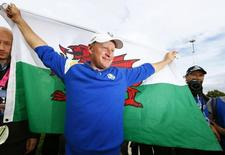 Team Europe golfer Jamie Donaldson celebrates with a Welsh flag after winning his match against U.S. player Keegan Bradley to retain the Ryder Cup for Europe on the 15th green during the 40th Ryder Cup at Gleneagles in Scotland September 28, 2014.      REUTERS/Eddie Keogh