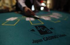 A logo of Japan casino school is seen as a dealer puts cards on a mock blackjack casino table, during a photo opportunity at an international tourism promotion symposium in Tokyo in this September 28, 2013 file photograph. REUTERS/Yuya Shino/Files
