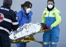 Imigrante é carregado por resgatistas ao chegar à cidade italiana de Augusta, na Sicília. 21/03/2014 REUTERS/Antonio Parrinello