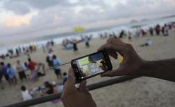 Policial no Rio de Janeiro mostra Neymar em seu celular enquanto assiste à jogo da Copa do Mundo de 2014. REUTERS/Nacho Doce