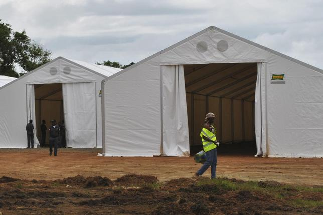A woman (R) walks at the construction site of an Ebola virus treatment centre at the Samuel K. Doe sports complex in Monrovia September 27, 2014.  REUTERS/James Giahyue