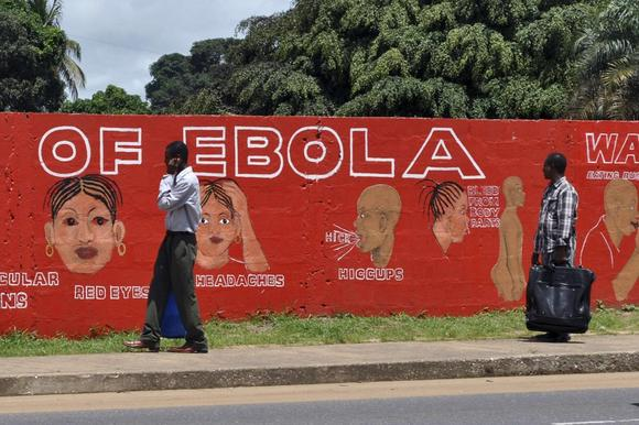 Pedestrians walk past a mural showing the symptoms of the Ebola virus in Monrovia, Liberia, September 26, 2014. REUTERS/James Giahyue