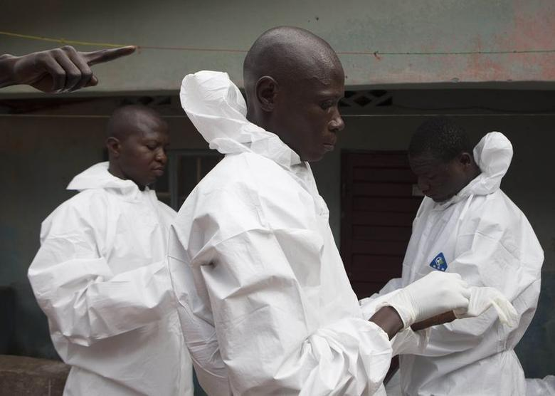A burial team wearing protective clothing, prepare to enter the home a person suspected of having died of the Ebola virus, in Freetown September 28, 2014. REUTERS/Christopher Black/WHO/Handout via Reuters