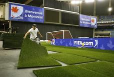 A worker puts down turf at Olympic Stadium in Montreal in preparation for the FIFA  U-20 World Cup soccer tournament, June 28, 2007.  REUTERS/Shaun Best
