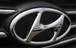 Kia cars are reflected in the Hyundai auto logo at a shipping yard of South Korea's biggest automakers Hyundai Motor Co and sister company Kia Motors at a port in Pyeongtaek July 21, 2014.   REUTERS/Kim Hong-Ji