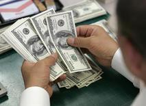Сотрудник банка Korea Exchange Bank считает долларовые купюры в Сеуле 3 сентября 2008 года. Курс доллара к иене растет накануне публикации отчета о занятости в США в сентябре. REUTERS/Jo Yong-Hak
