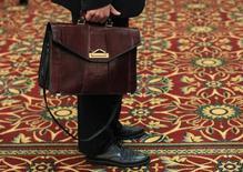 Un hombre sujeta un maletín mientras espera en línea en una feria laboral en Melville, Nueva York . Imagen de archivo, 19 julio, 2012. Los empleadores estadounidenses probablemente intensificaron las contrataciones en septiembre y la tasa de desempleo probablemente se mantuvo en un mínimo de seis años, lo que podría reforzar las apuestas por una subida de tasas de interés de la Reserva Federal a mediados del 2015. REUTERS/Shannon Stapleton