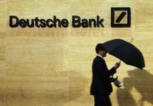 Un hombre pasa frente al logo del Deutsche Bank en Londres. Imagen de archivo, 05 diciembre, 2013. Deutsche Bank tuvo un buen desempeño en el tercer trimestre, en especial en su banca minorista y de inversiones, ayudándole a asumir los cargos que enfrenta por temas legales y regulatorios, dijeron a Reuters dos fuentes financieras cercanas al asunto.   REUTERS/Luke MacGregor