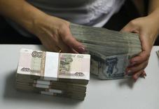 Сотрудница банка пересчитывает рублевые купюры в Москве 2 сентября 2014 года. Министерство финансов РФ нашло в бюджете для попавшего под  санкции Россельхозбанка дополнительно 5 миллиардов рублей в капитал в этом году. REUTERS/Maxim Zmeyev