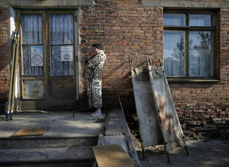 A woman smokes next to blood-stained stretchers placed to dry in the sun at the hospital in Schastya, near the eastern Ukrainian town of Luhansk October 7, 2014. REUTERS/David Mdzinarishvili