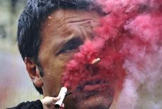 Manifestante coloca sinalizador em frente a cartaz com foto de premiê italiano Renzi em Milão. 08/10/2014 REUTERS/Stefano Rellandini