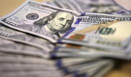 Долларовые купюры в Йоханнесбурге 13 августа 2014 года. Курс доллара к корзине шести основных валют снизился до двухнедельного минимума после публикации протокола совещания ФРС, из которого инвесторы сделали вывод, что повышение процентных ставок может быть отложено. REUTERS/Siphiwe Sibeko