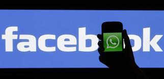 Un hombre sujeta un smartphone mostrando el logo de Wastsapp frente a una pantalla con el logo de Facebook en Praga. Imagen de archivo, 20 febrero, 2014. Facebook Inc, que el lunes completó su adquisición de WhatsApp, no tiene planes a corto plazo para materializar ingresos del servicio de mensajería en móviles, dijo el jueves  su presidente ejecutivo, Mark Zuckerberg.  REUTERS/David W Cerny