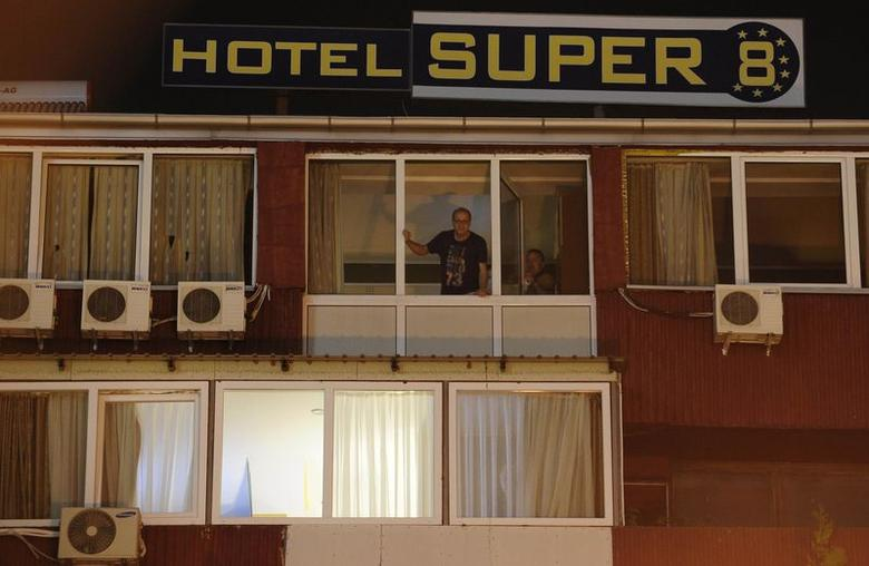 People look from the window of a quarantined hotel in Skopje October 9, 2014.  REUTERS/Ognen Teofilovski
