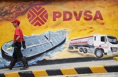 Un trabajador pasa por un mural de PDVSA en una estación gasolinera en Caracas. Imagen de archivo, 29 agosto, 2014. La estatal Petróleos de Venezuela (PDVSA) prepara un canje masivo de bonos para aliviar la pesada carga de su deuda financiera a vencerse en los próximos años, dijo a Reuters una alta fuente de la petrolera conocedora del tema. REUTERS/Carlos Garcia Rawlins