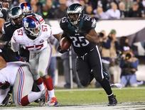 Oct 12, 2014; Philadelphia, PA, USA; Philadelphia Eagles running back LeSean McCoy (25) runs past New York Giants linebacker Jacquian Williams (57) during the first quarter at Lincoln Financial Field.  Bill Streicher-USA TODAY Sports