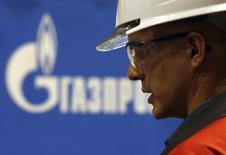 """Рабочий на фоне логотипа Газпрома на заводе ОМК в Выксе 15 апреля 2014 года. Газпром говорит, что ему еще только предстоит подписать межправительственное соглашение о поставках газа в Китай по """"восточному"""" маршруту, которое предполагает продажу топлива на $400 миллиардов. REUTERS/Sergei Karpukhin"""