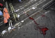 """Кровь и носилки на тротуаре рядом с площадью Независимости в Киеве 20 февраля 2014 года. Для миллионов украинцев это стало преступлением против человечности. В феврале более сотни демонстрантов были застрелены во время восстания на майдане, стоившего президентского кресла Виктору Януковичу. Жертвы теперь известны как """"небесная сотня"""". REUTERS/Maks Levin"""