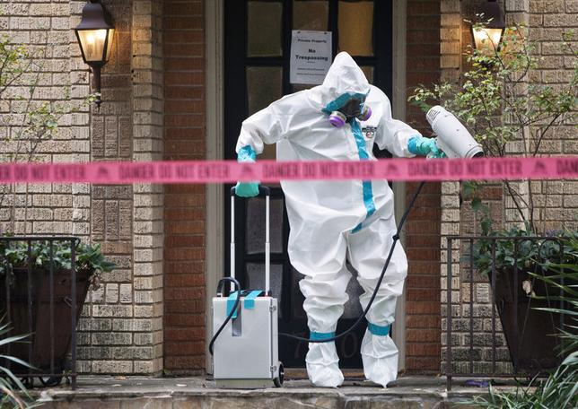 10月12日、米CDCは、ダラスの病院でエボラ出血熱治療に関わっていた看護師が感染しているのを確認したと発表。写真は看護師の自宅玄関を消毒する衛生当局者(2014年 ロイター/Jaime R. Carrero)
