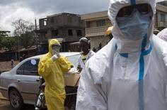 Медики в защитных костюмах у больницы во Фритауне 6 октября 2014 года. Президент США Барак Обама в среду проведёт видеоконференцию с лидерами Великобритании, Франции, Германии и Италии, чтобы обсудить эпидемию лихорадки Эбола в Западной Африке и другие острые международные проблемы, сообщил Белый дом. REUTERS/Christopher Black/WHO/Handout via Reuters