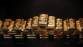 Слитки золота в хранилище ProAurum в Мюнхене 6 марта 2014 года. Цены на золото снижаются на фоне подъема доллара и котировок акций, но опасения за состояние мировой экономики продолжают поддерживать рынок. REUTERS/Michael Dalder