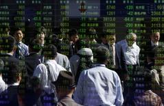 Peatones son reflejados en una pantalla electrónica que muestra índices económicos en Tokio, 17 octubre, 2014. Las bolsas de Asia cedían el viernes, incapaces de mantener unas ganancias iniciales luego de que unos sólidos datos estadounidenses sólo dieron un impulso temporal y no lograron disipar las preocupaciones subyacentes sobre la desaceleración del crecimiento económico mundial. REUTERS/Yuya Shino