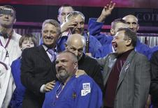 Businessmen Boris Rotenberg (L, front, wearing a black jacket) and Arkady Rotenberg (R, front, wearing a grey jacket) react during an awarding ceremony of a judo competition in St. Petersburg, in this February 27, 2012 file photo. Picture taken February 27, 2012. TO MATCH UKRAINE-CRISIS/SANCTIONS-ROTENBERG REUTERS/Stringer (RUSSIA  - Tags: POLITICS BUSINESS)